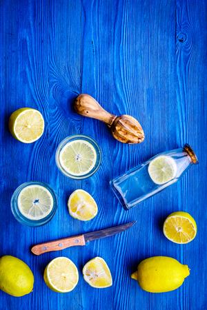 Fresh homemade lemonade. Lemons, juicer, glass for beverage on blue wooden background top view.
