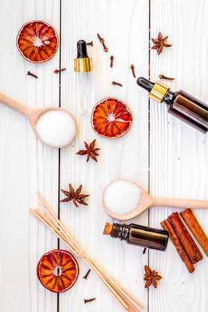 Aromatherapy for relax concept. Spa salt, candles and oil with spices cinnamon, badian and citrus on white wooden background top view Stock Photo