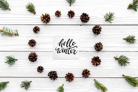 Hello winter hand lettering. Winter pattern with pinecones and spruce branch on white wooden background top view