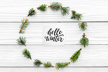 Hello winter hand lettering with hat icon. Winter pattern with spruce branches on white wooden background top view Stock Photo