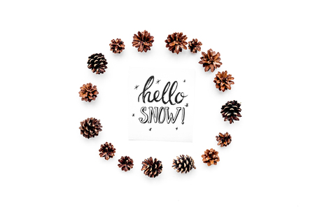 Hello snow hand lettering. Winter pattern with pinecones on white background top view Imagens