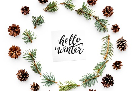 Hello winter hand lettering. Winter pattern with spruce branches and pinecones on white background top view 版權商用圖片