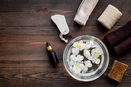 Bath in bowl with tropical flowers for foot spa, pumice stone, soap and oil on dark wooden background top view copyspace