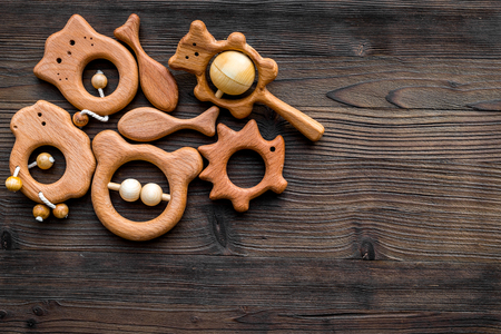 Cute wooden handmade toys for newborn on dark wooden background top view copyspace