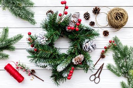 クリスマス リースを作る。小ぎれいなな枝、コーン、スレッド、麻ひも、白い木製の背景上面にハサミを持って駆け回る