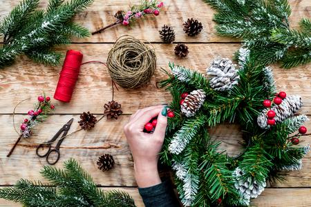 Hände machen Weihnachtskranz. Fichtenzweige, Kegel, Threads, Schnur, Sciccors auf Draufsicht des hellen hölzernen Hintergrundes. Standard-Bild - 90216365