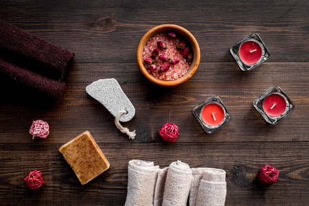 Floral foot spa with rose. Candles, salt, pumice stone, soap, buds on dark wooden background top view Stock Photo