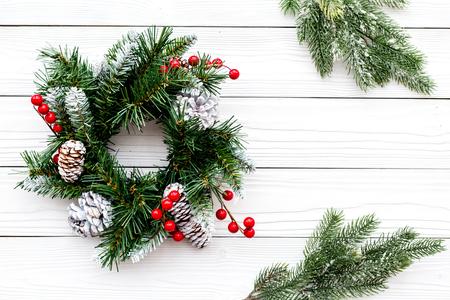 Weihnachtskranz gewebt von Fichtenzweigen mit roten Beeren auf weißem hölzernem Hintergrund Draufsicht Standard-Bild - 90216368