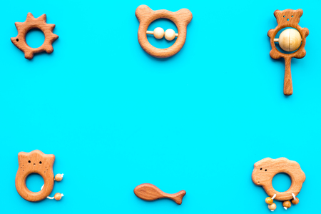 Simple handmade toys for newborn baby in shape of animals on turquoise background top view copyspace