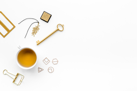 Office desk in trendy gold color. Glittering stationery near cup of tea   on white background top view copyspace