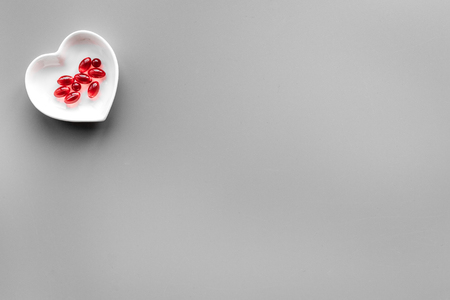 Treat heart. Pills in bowl in shape of heart on grey background top view copyspace Stock Photo