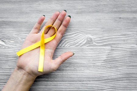 Woman hand hold yellow ribbon for suicide and endometriosis awareness on grey wooden background top view copyspace Stock Photo