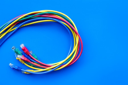 Network colored cables for computer on blue background top view copyspace Stock Photo - 90304501