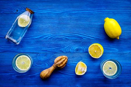 Fresh homemade lemonade. Lemons, juicer, glass for beverage on blue wooden background top view copyspace Stock Photo