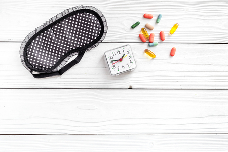 Combat insomnia. Sleeping pills near sleep mask and alarm clock on white wooden background top view copyspace