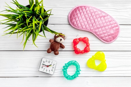 Healthy sleep for children. Sleep mask, plant, alarm clock, toys on white wooden background top view