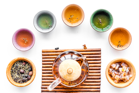 Tea ceremony concept. Tea pot on bamboo mat, cups, dry tea leaves, sugar on white background top view