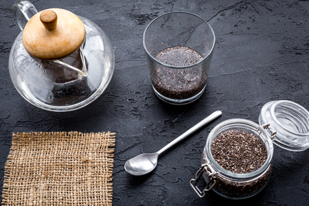 Brew chia seeds. Jar with seeds, scoop, bowl, tea pot with hot water. Black background