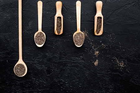 Superfood chia seeds in a wooden spoon and scoop on black background top view copyspace