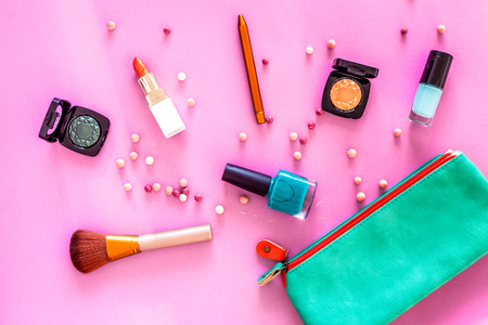 Content of cosmetic bag. Lipstick, eye shadows, nail polish, rouge, brushes for makeup on pink background top view. Фото со стока - 90299565