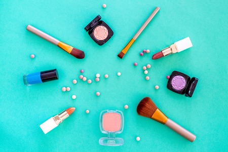 Set of decorative cosmetics. Lipstick, eye shadows, nail polish, rouge, brushes for makeup on blue background top view Stock Photo