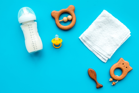 Little baby background. Wooden toys, pacifier, bottle, towel on blue background top view copyspace