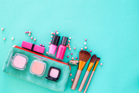 Content of cosmetic bag. Lipstick, eye shadows, nail polish, rouge, brushes for makeup on blue background top view copyspace