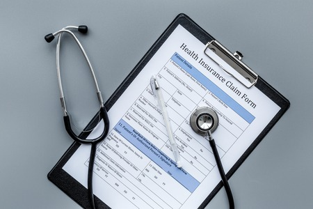 Health insurance for reception at the doctor. Document and stethoscope on dark grey background top view