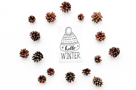 Hello winter hand lettering with hat icon. Winter pattern with pinecones on white background top view