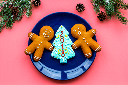 Cookies for New Year. Gingerbread man and spruce with lettering 2018 near spruce branch on pink background top view
