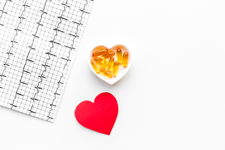 Treat heart. Pills in bowl in shape of heart and cardiogram on white background top view.