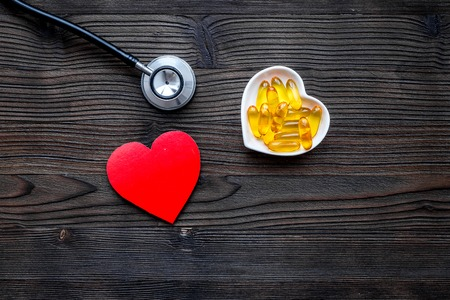 Treat heart. Pills in bowl in shape of heart on dark wooden background top view.