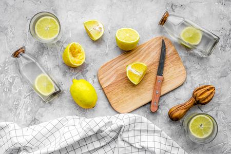 Prepare refreshing beverage lemonade. Lemons, juicer, bottle, knife, cutting board on grey stone background top view.