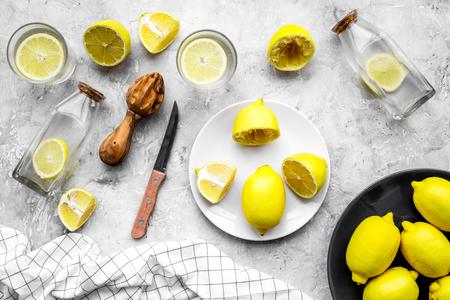 Fresh homemade lemonade. Lemons, juicer, glass for beverage on grey stone background top view.