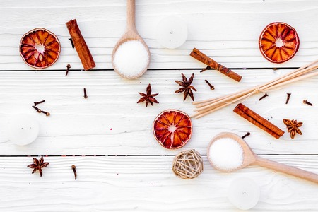 Aromatherapy for relax concept. Spa salt, candles and oil with spices cinnamon, badian and citrus on white wooden background top view.