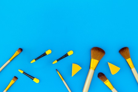 Set of brushes for makeup and eyeshadow applicator on blue background top view.