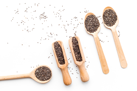 Superfood chia seeds in a wooden spoon and scoop on white background top view.