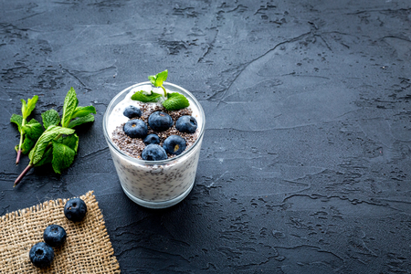 Light dessert with chia seeds, yogurt, blueberry and mint. Black background. Stock Photo