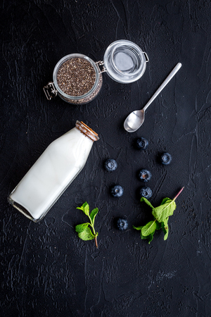 Light dessert with chia seeds, yogurt, blueberry and mint. Black background top view.