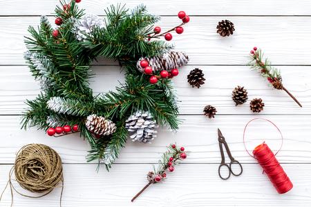 Weihnachtskranz machen. Fichtenzweige, Kegel, Threads, sciccors auf Draufsicht des weißen hölzernen Hintergrundes. Standard-Bild - 90405642