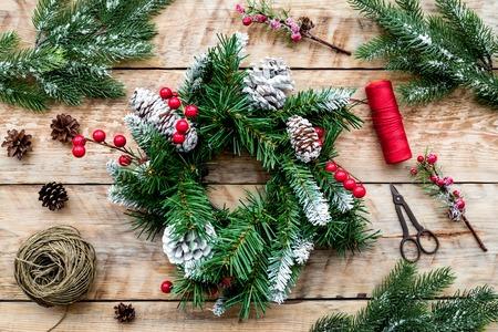 Machen Sie Weihnachtskranz. Fichtenzweige, Kegel, Threads, Schnur, Sciccors auf Draufsicht des hellen hölzernen Hintergrundes. Standard-Bild - 90405645