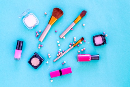 Set of decorative cosmetics. Lipstick, eye shadows, nail polish, rouge, brushes for makeup on blue background top view.