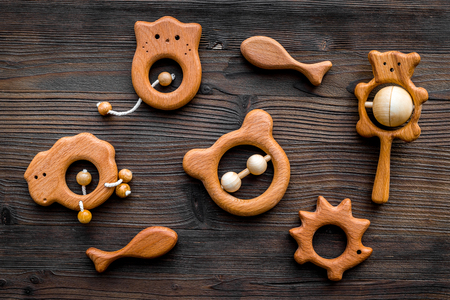 Cute wooden handmade toys for newborn on dark wooden background top view.