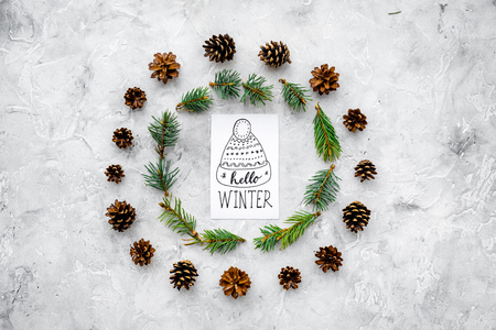 Hello winter hand lettering. Winter pattern with pinecones and spruce branch on grey background top view. Imagens - 90405822