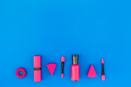 Bright decorative cosmetics. Pink nail polish and lipstick on blue background top view. Stock Photo