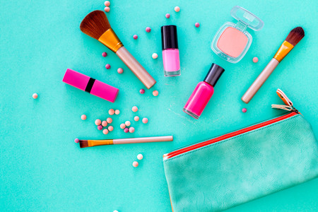 Content of cosmetic bag. Lipstick, eye shadows, nail polish, rouge, brushes for makeup on blue background top view. Stock Photo
