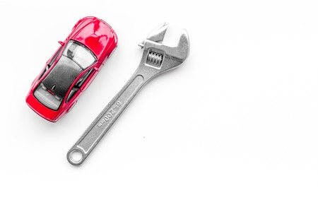 Car repair concept. Wrench near car toys on white background top view.
