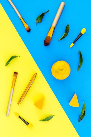 파란색과 노란색 배경 상위 뷰 메이크업 및 아이 섀도우 주걱에 브러쉬 세트. 스톡 콘텐츠 - 90405884