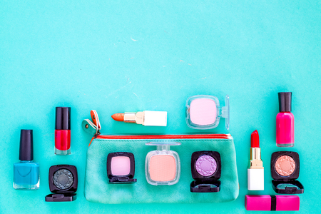 Content of cosmetic bag. Lipstick, eye shadows, nail polish, rouge on blue background top view.