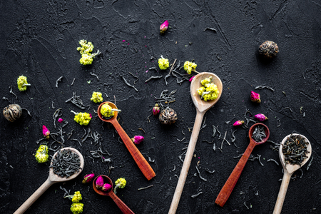 Aromatic tea. Wooden spoons with dried tea leaves, flowers and spices on black background top view.